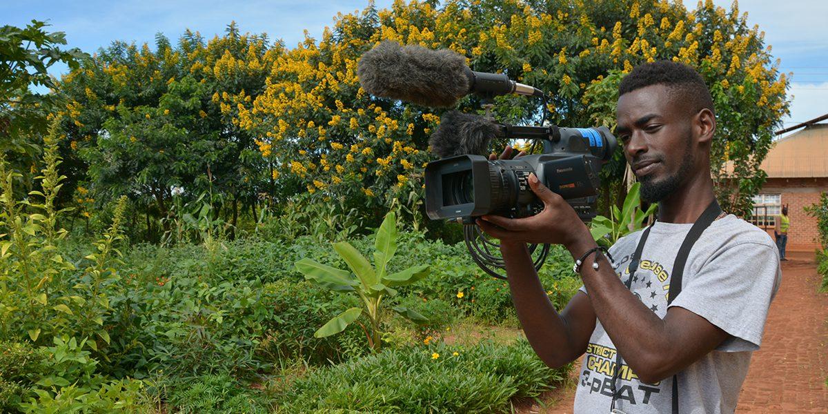 Hugo, journaliste communautaire en action avec sa caméra dans le camp de réfugiés Dzaleka (JRS)
