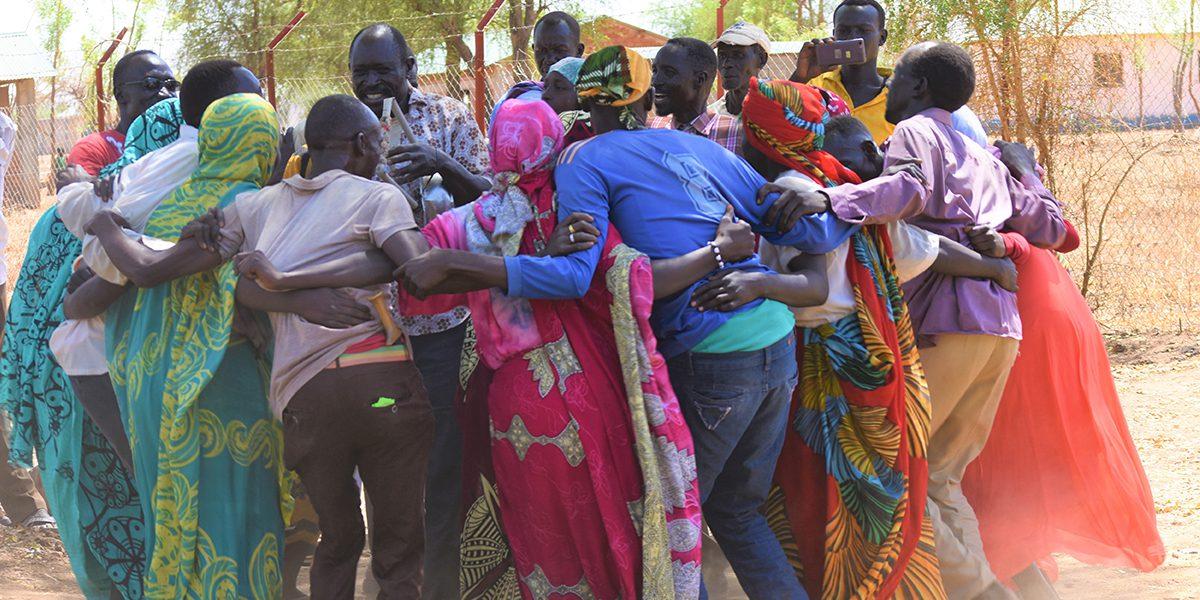 Un groupe d'adulte danse, chante et frappe du pied dans un cercle alors qu'ils se préparent à fêter la Journée internationale de la femme à Maban, Soudan du Sud (Paul Jeffrey/Misean Cara)