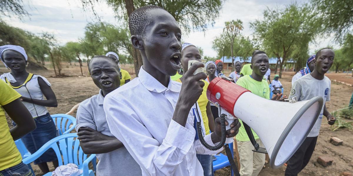 Avec un mégaphone, un homme conduit un groupe de réfugiés chantant pendant une activité sponsorisée par JRS dans le camp de réfugiés de Doro à Maban, Soudan du Sud.