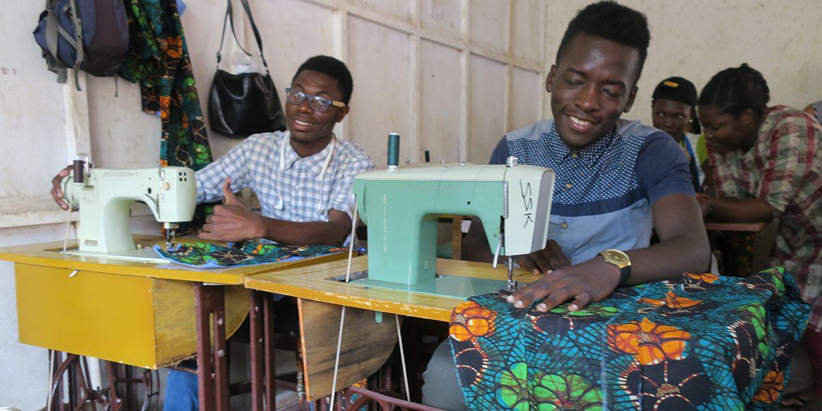 Deux étudiants travaillent avec diligence pour devenir tailleurs, à JRS Kampala (JRS)