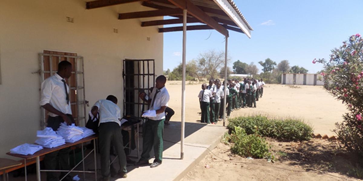 Des étudiants rangés attendent leur tour pour recevoir leur nouvel uniforme scolaire (JRS)