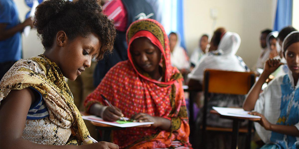 Des étudiants écrivent des cartes postales à destination de Londres, à une classe qui avait envoyé des cartes dans le cadre du projet 'Any Refugee' (JRS)