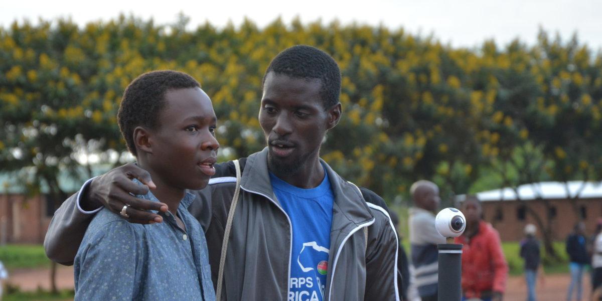 Deux réfugiés prennent du repos au cours d'un match de basket au camp pour réfugiés de Dzaleka (Service Jésuite des Réfugiés)